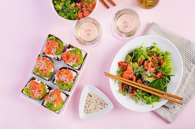 Colazione salutare. ciotola di buddha con riso, mango, avocado e salmone salmone con sandwich di avocado