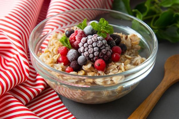 Colazione salutare con avena, frutti di bosco e menta. porridge di avena con frutta.