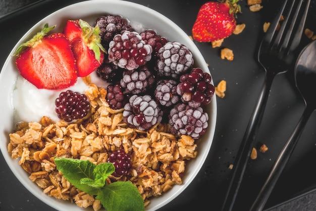 Colazione salutare. frutti e bacche estive. yogurt greco fatto in casa con muesli, more, fragole e menta. tavolo in pietra nera, con gli ingredienti.