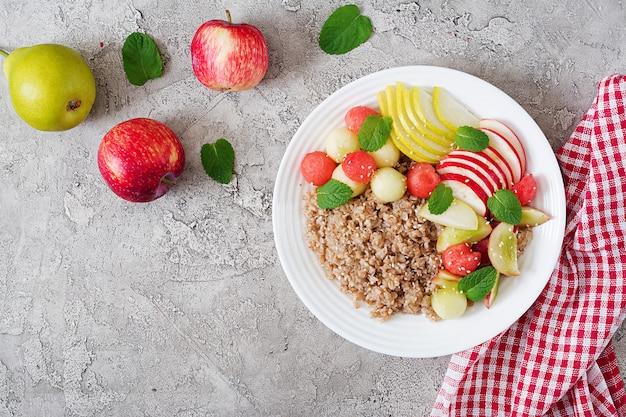 Colazione salutare. grano saraceno o porridge con melone fresco, anguria, mela e pera.