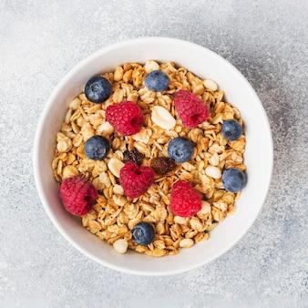 Colazione salutare. granola fresco, muesli con yogurt e frutti di bosco sul tavolo grigio. copia spazio