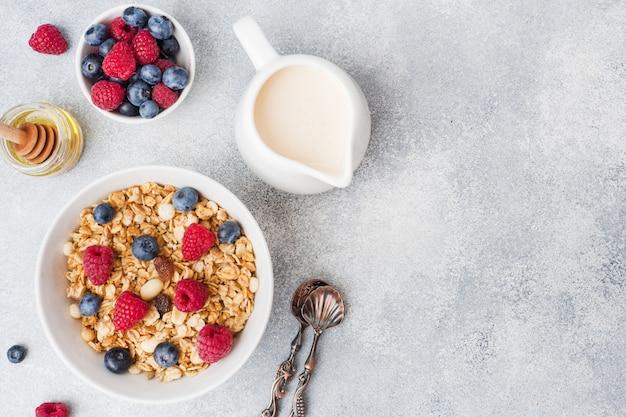 Colazione salutare. muesli fresco, muesli con yogurt e frutti di bosco su sfondo grigio. copia spazio