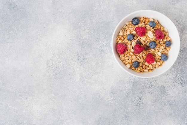 Colazione salutare. muesli fresco, muesli con yogurt e frutti di bosco su sfondo grigio.