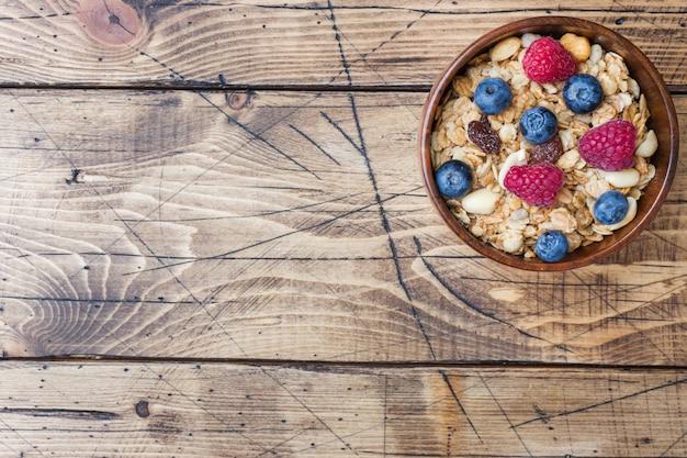 Colazione salutare. muesli fresco, muesli con yogurt e frutti di bosco su superficie di legno