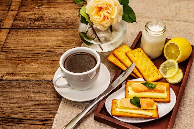 Colazione salutare. tazza di caffè (tè nero), latte, crackers con burro e salmone
