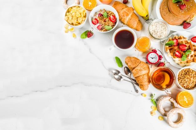 Colazione sana concetto di mangiare, vari cibi mattutini - frittelle, cialde, cornetti sandwich di farina d'avena e muesli con yogurt, frutta, bacche, caffè, tè, succo d'arancia, sfondo bianco