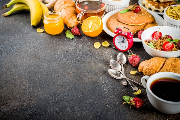 Colazione sana concetto di mangiare, vari cibi mattutini - frittelle, cialde, cornetti sandwich di farina d'avena e muesli con yogurt, frutta, bacche, caffè, tè, succo d'arancia