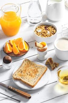 Colazione sana concetto di mangiare, vari cibi mattutini - frittelle, uovo alla coque, toast, farina d'avena, muesli, frutta, caffè, tè, succo d'arancia, latte sul tavolo di legno bianco