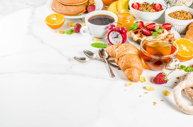 Colazione sana concetto di mangiare, vari cibi mattutini - frittelle, waffle, sandwich di farina d'avena croissant e muesli con yogurt, frutta, bacche, caffè, tè, succo d'arancia, sfondo bianco