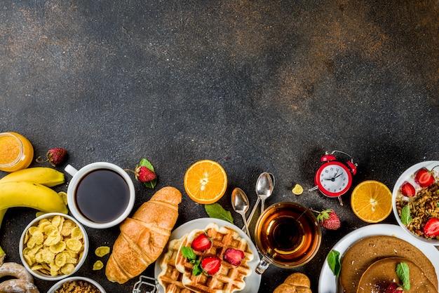 Colazione sana mangiare concetto, vari cibi mattutini - frittelle, cialde, cornetti sandwich di farina d'avena e muesli con yogurt, frutta, bacche, caffè, tè, succo d'arancia
