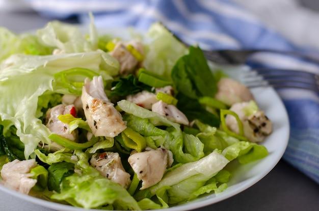 Colazione sana o pranzo insalata di verdure fresche di lattuga iceberg, porro e petto di pollo.