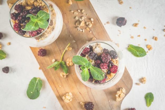 Colazione sana vegana dietetica. yogurt e muesli con arance fresche e menta in un bicchiere. su un tavolo bianco su un tagliere.