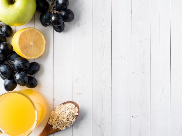 Colazione su un tavolo bianco caffè croissant succo d'arancia uva mela cioccolato