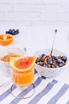 Colazione su uno sfondo bianco in legno. muesli con frutti di bosco e succo d'arancia. copia spazio