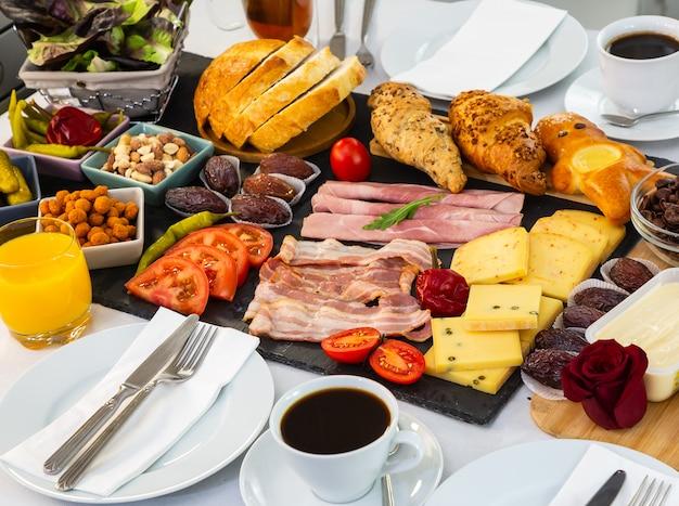 Colazione sul tavolo. colazione a base di croissant, cereali, pancetta, prosciutto, formaggio, lattuga, fagioli, fiocchi di mais, frutta, caffè, tè e succo d'arancia. , pranzo o cena per tutti i giorni