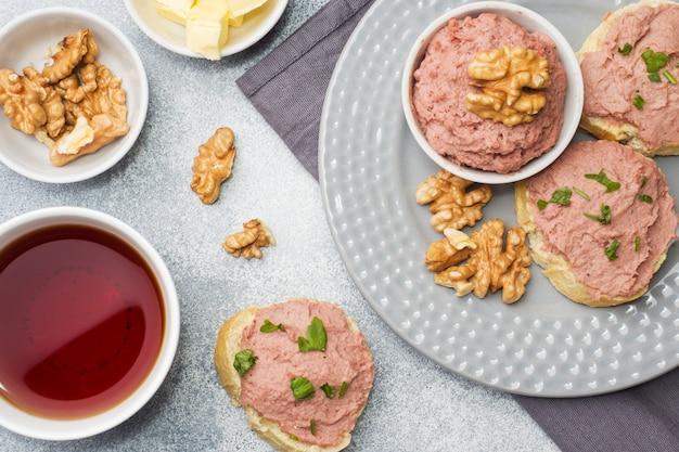 Colazione sul tavolo patè di pollo e panini al burro. tazza di tè