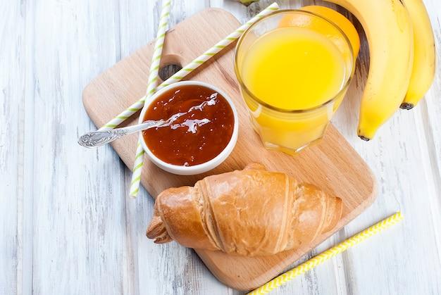Colazione tradizionale con cornetto e marmellata, succo d'arancia