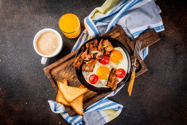 Colazione tradizionale inglese americano fatta in casa, uova fritte, toast, pancetta, con tazza di caffè