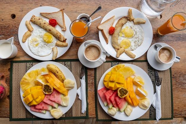 Colazione tropicale a base di frutta, caffè e uova strapazzate e pancake alla banana per due sulla spiaggia vicino al mare. vista dall'alto, impostazione della tabella.