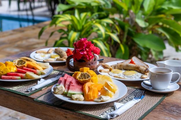 Colazione tropicale a base di frutta, caffè e uova strapazzate e pancake alla banana per due sulla spiaggia vicino al mare