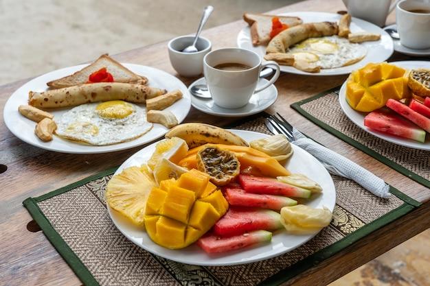 Colazione tropicale a base di frutta, caffè e uova strapazzate e pancake alla banana