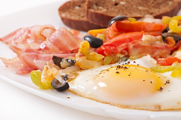 Colazione - uova fritte con pancetta, pomodori, olive e fette di formaggio