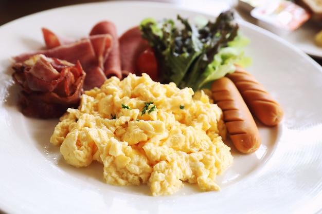 Colazione uova strapazzate con pancetta salsiccia e insalata su fondo di legno