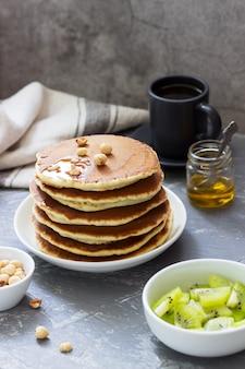 Colazione vegetariana a base di pancake, caffè, miele, noci e frutta.