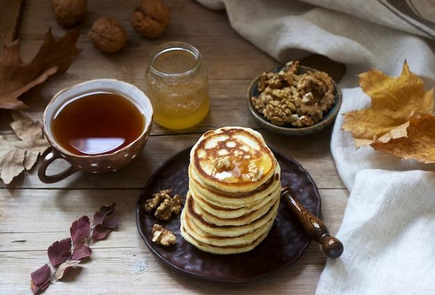 Colazione vegetariana di frittelle con miele, noci e tè. natura morta autunnale.
