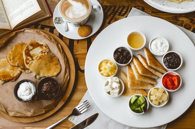 Colazione vista dall'alto set frittelle con crema al cioccolato e toast alla panna acida con marmellata crema al cioccolato miele cetriolo pomodoro burro e tazza di caffè sul tavolo