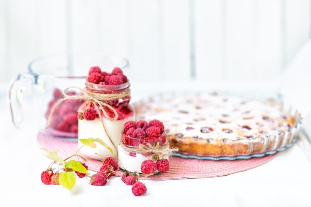 Colazioni, dolci. yogurt con sciroppo di lamponi e bacche di lampone e torta di lamponi