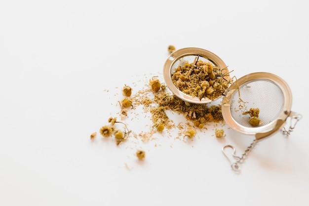 Colino metallico del tè sulla tavola bianca