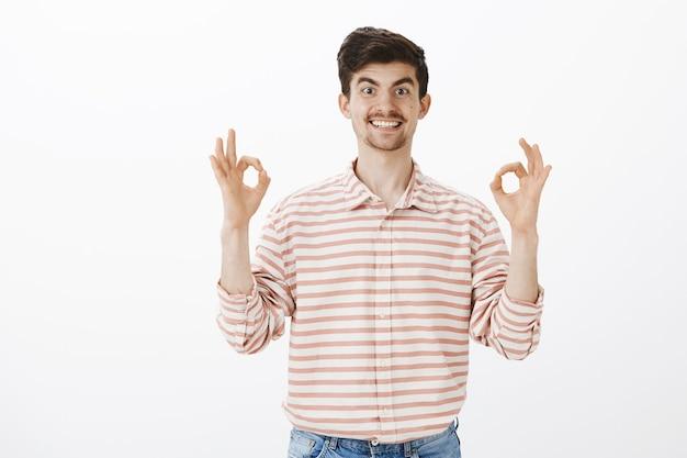 Collaboratore disponibile pronto ad aiutare. ritratto di uomo europeo energico ed amichevole con i baffi, alzando le mani e mostrando segno ok o grande, approvando l'idea ed essendo felice di garantire un amico oltre il muro grigio