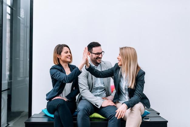 Collaboratori di alto cinque dopo una startup di successo.