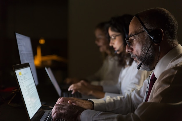 Collaboratori focalizzati in cuffie digitando su computer portatili