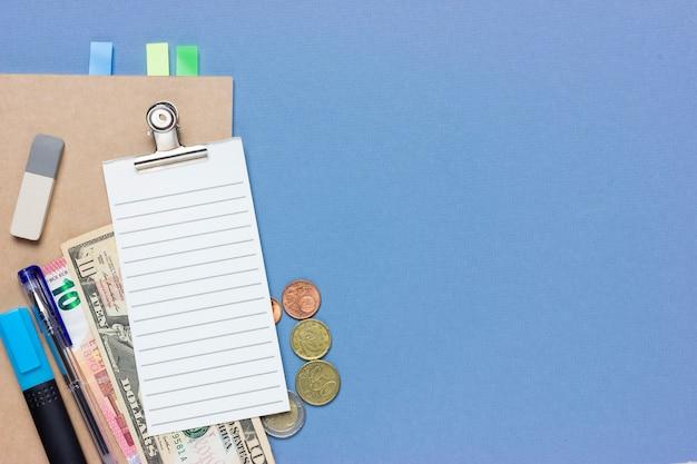 Collage di concetto su un tema finanziario. pianificare un budget o fare shopping. lista di controllo, monete, 10 euro, dollaro, monete, articoli di cancelleria. sfondo blu e luogo per il testo.