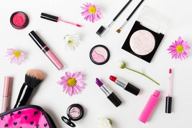 Collage di cosmetici colorati femminili sulla scrivania bianca