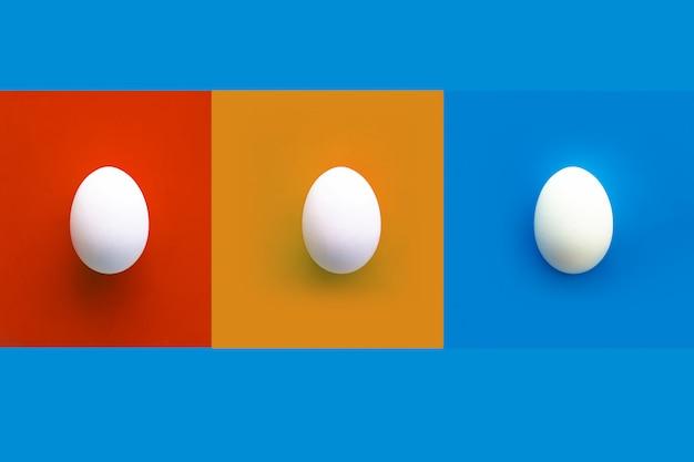 Collage di rettangoli rossi, arancioni e blu con tre uova bianche di pollo.
