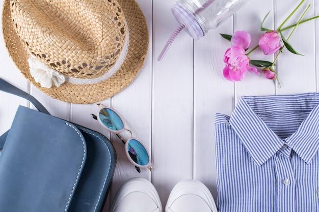 Collage di vestiti e accessori estate donna piatta laici su bianco con camicia, jeans, occhiali, scarpe, borsa, cappello, vaso