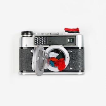 Collage fatto di macchina fotografica d'epoca e lavatrice con vestiti