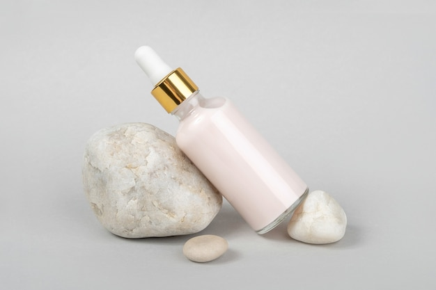 Collagene rosa antietà, siero viso in flacone di vetro trasparente con pipetta d'oro e pietre naturali su grigio