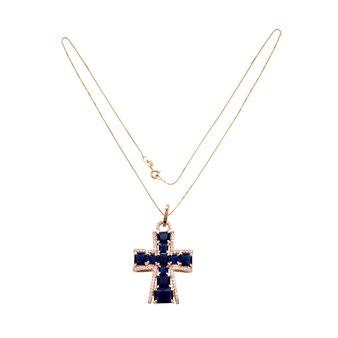 Collana a catena in oro con pendente a croce sulla superficie bianca
