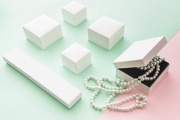 Collana di perle bianche con scatole bianche su sfondo pastello rosa e verde