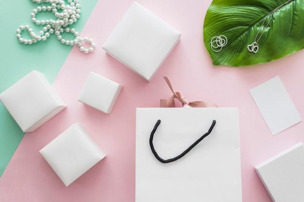 Collana di perle e molte scatole bianche con shopping bag su sfondo rosa