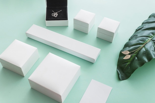 Collana e orecchini d'oro su fondo pastello con scatole bianche