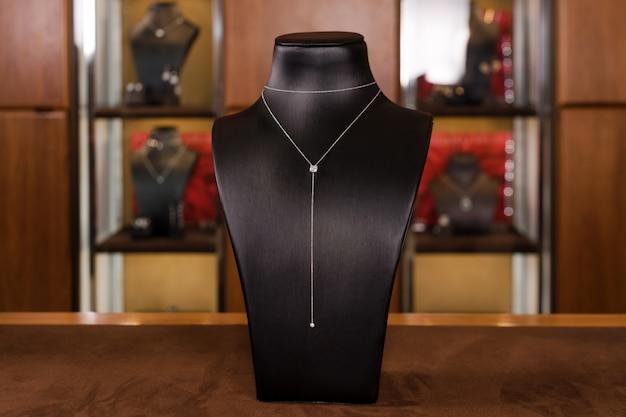 Collana in oro bianco con diamanti su un supporto nella boutique di gioielli di moda. collo nero con gioielli di lusso, accessori da donna nella vetrina del negozio.