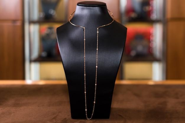 Collana in oro con diamanti su un supporto nella boutique di gioielli di moda. collo nero con gioielli di lusso, accessori da donna nella vetrina del negozio.