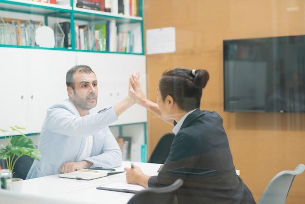 Collega di saluto del responsabile maschio sicuro con il gesto ciao-cinque
