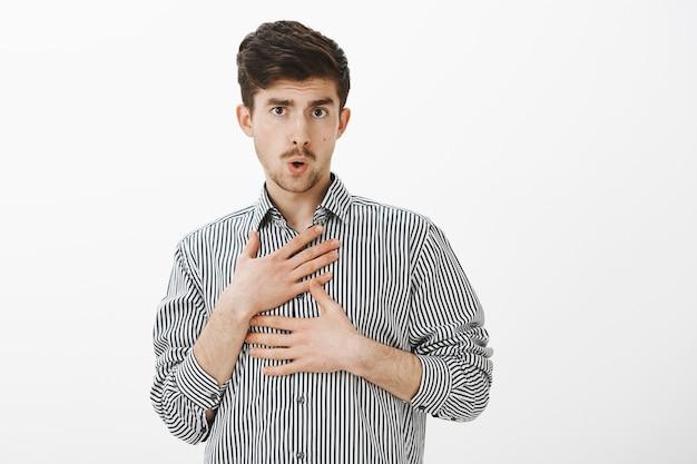 Collega maschio caucasico divertente ubriaco in camicia a righe, prendendo in giro il collega sciocco, piegando le labbra e toccandosi, tenendo le mani sul petto, essendo giocoso e sfocato sul muro grigio