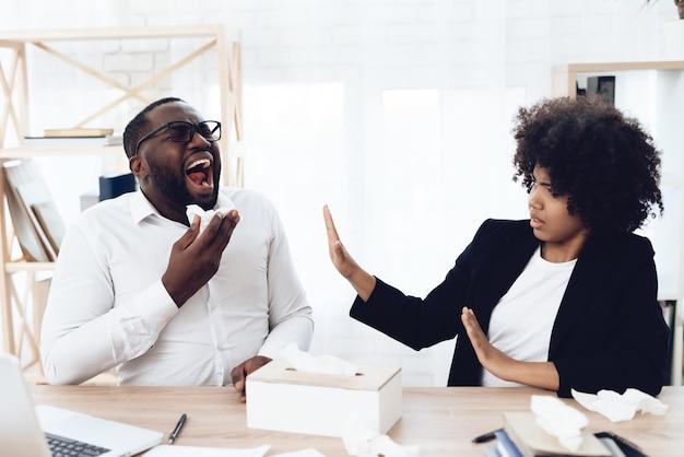 Colleghe africani che si siedono al tavolo con l'uomo che starnutisce.